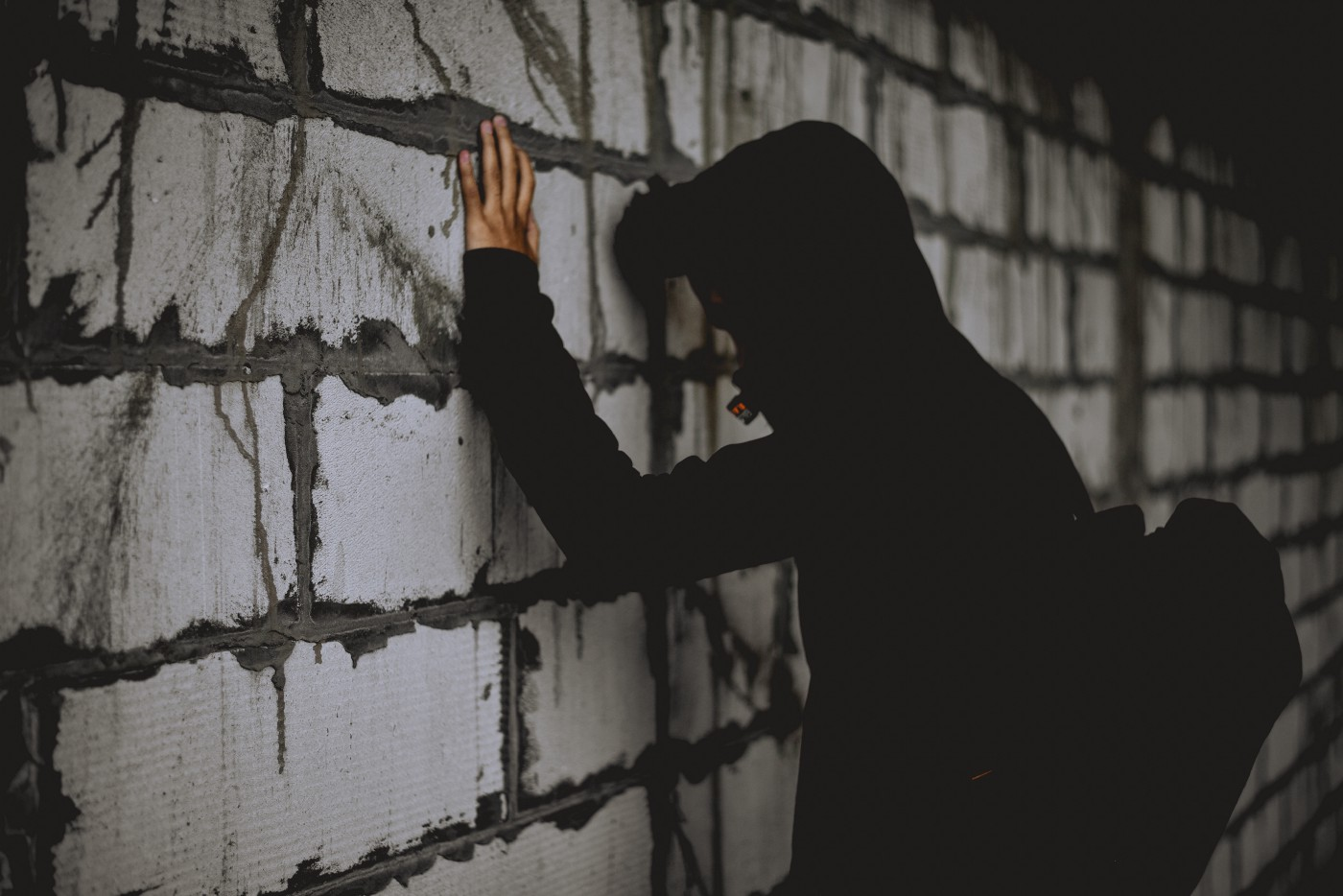 A man stands with his head facing a wall