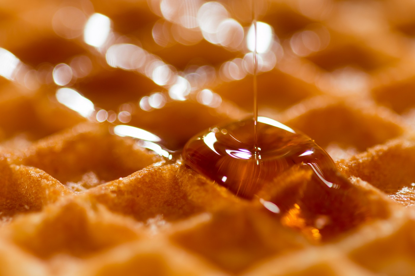 close up photo of waffle with syrup being poured on it