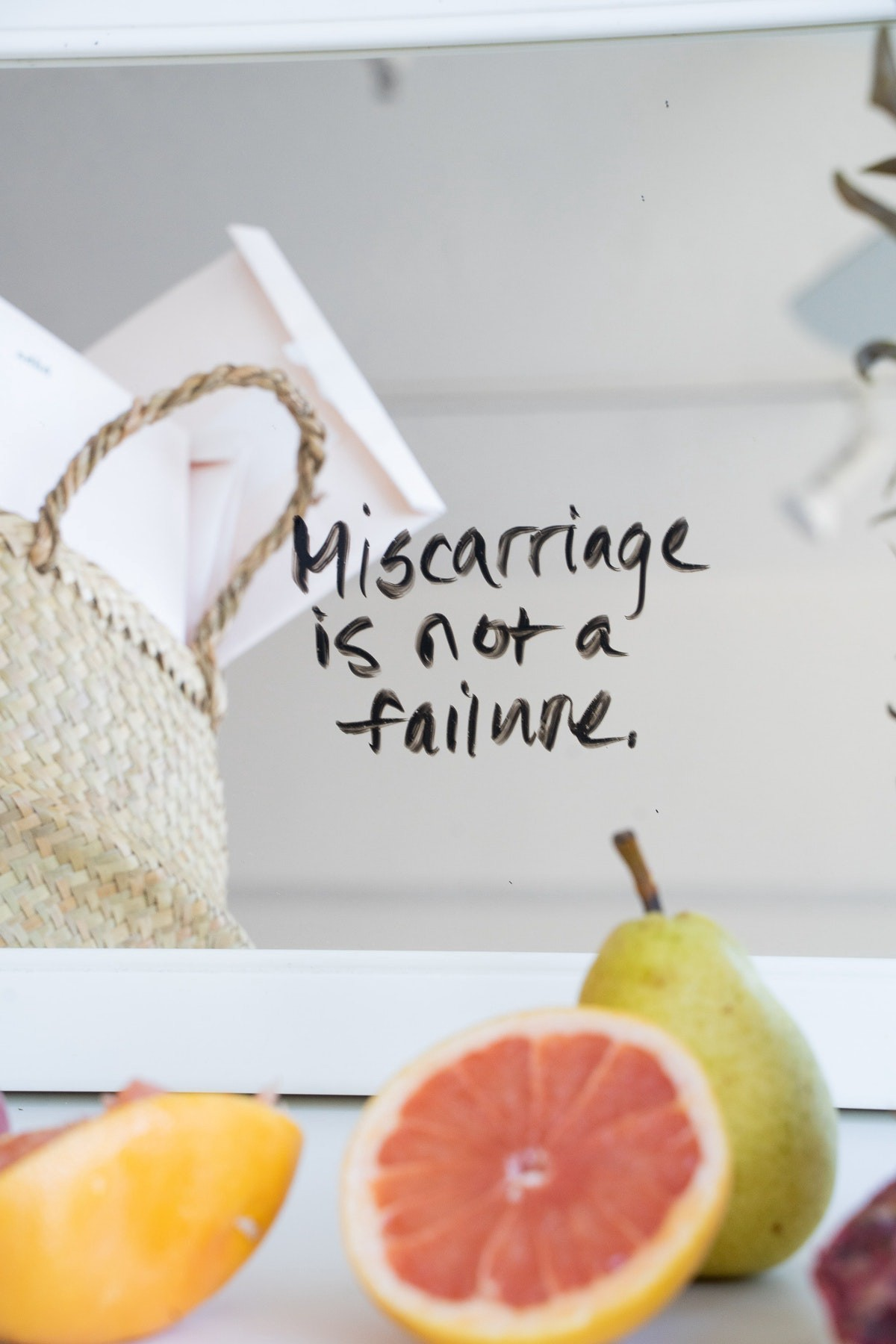 """a half of a grapefruit and a pear sitting on a kitchen counter. the words """"miscarriage is not a failure"""" are written above them in black ink"""
