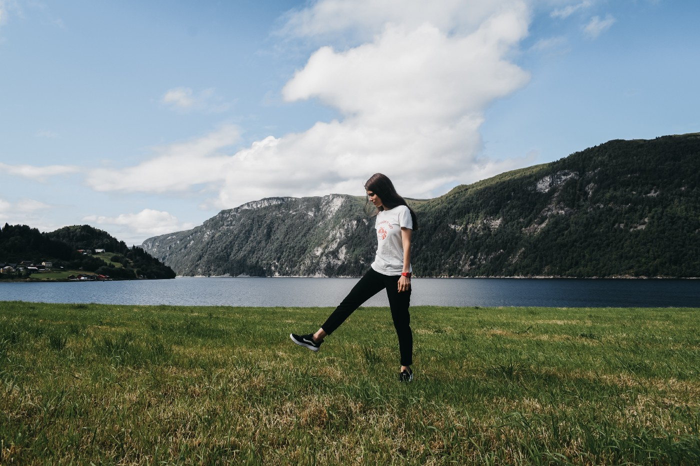 photo of young, casual woman walking along picturesque Norwegian fiord