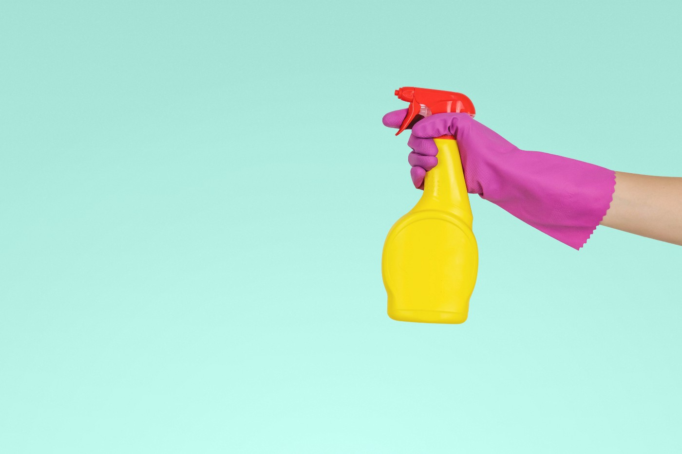 Pink-gloved hand holding yellow cleaning bottle with red top.