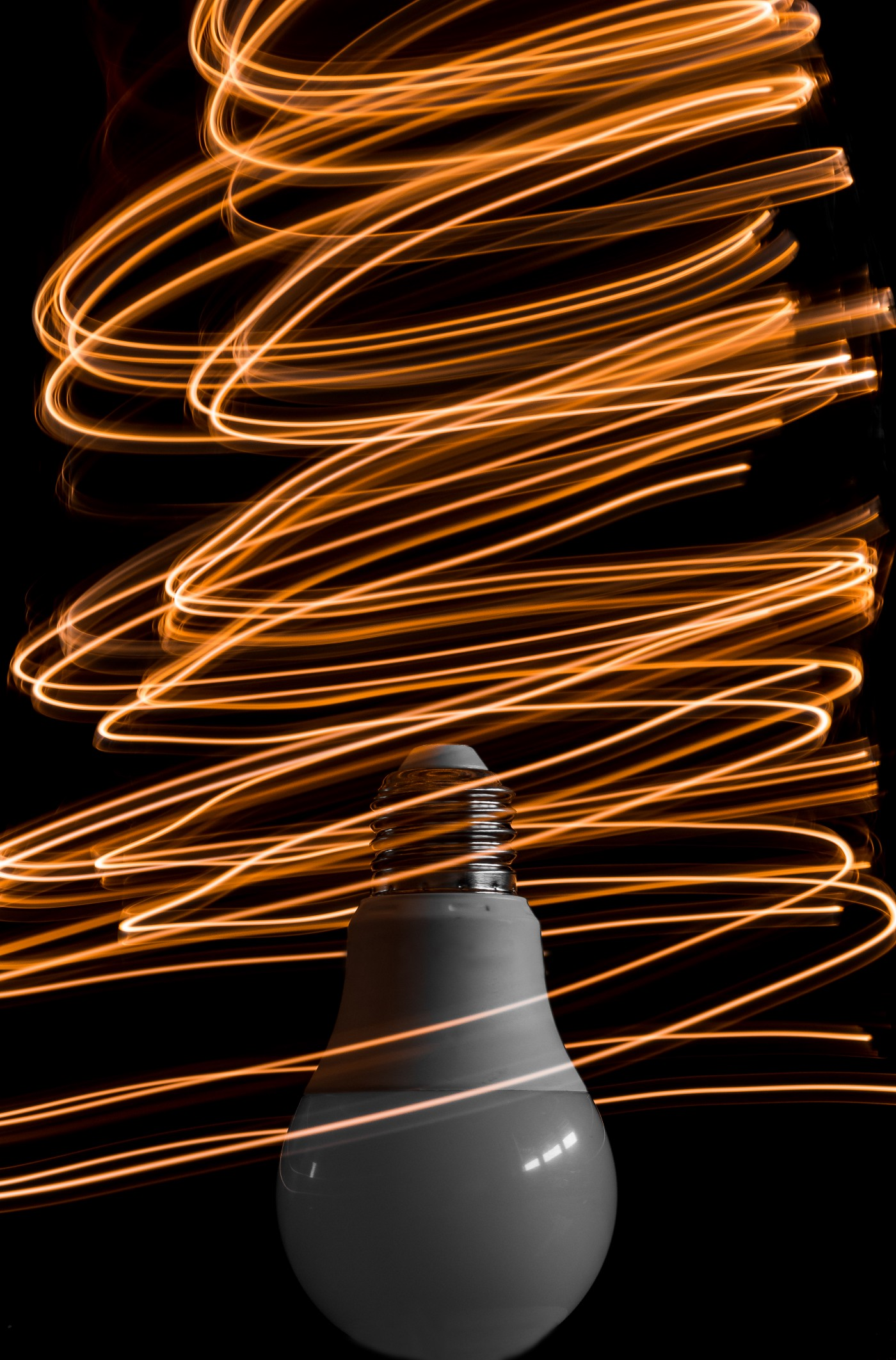 An upside down light bulb with a whirlwind of orange-yellow light surrounding it. Symbolic of ideas, innovation, and thinking outside the box. Defying the status quo.