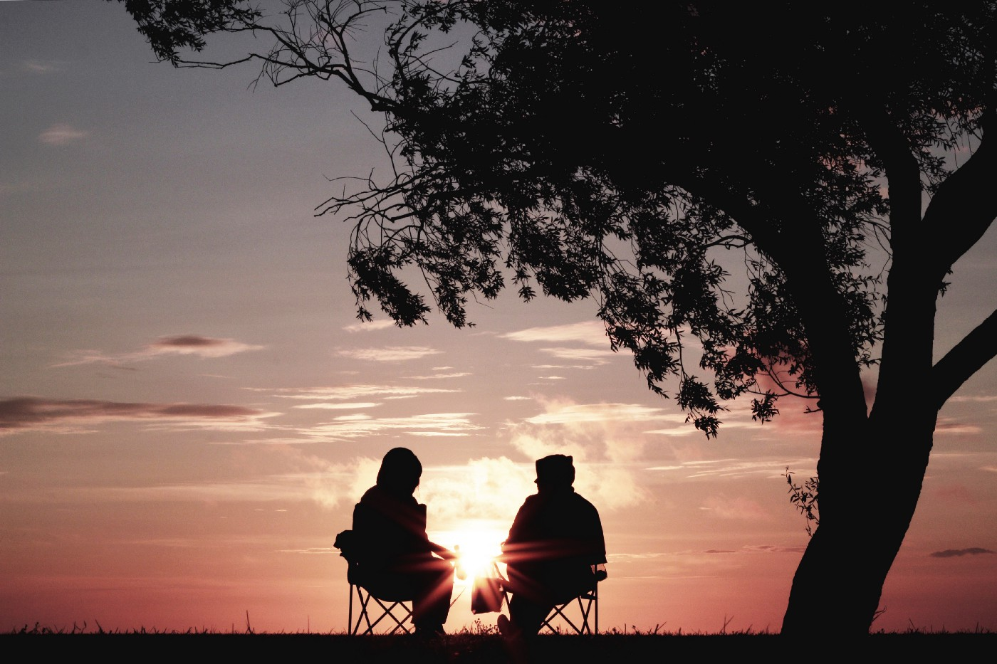 Two people sit under a tree, silhouetted against a sunset. There is a distance between them, with the sun showing between them as it lowers beyond the horizon.