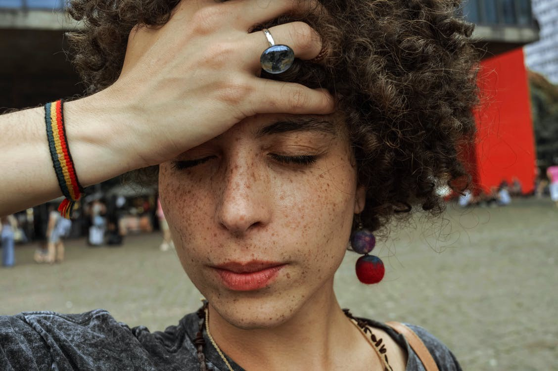 A person of color with freckles and a rainbow bracelet puts her hand over her forehead, seemingly stressed. #stress #anxiety