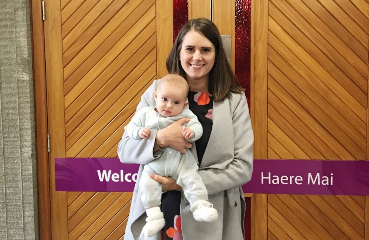 Aleisha, holding pēpi, in front of the wooden council doors which say 'Welcome—Haere Mai'