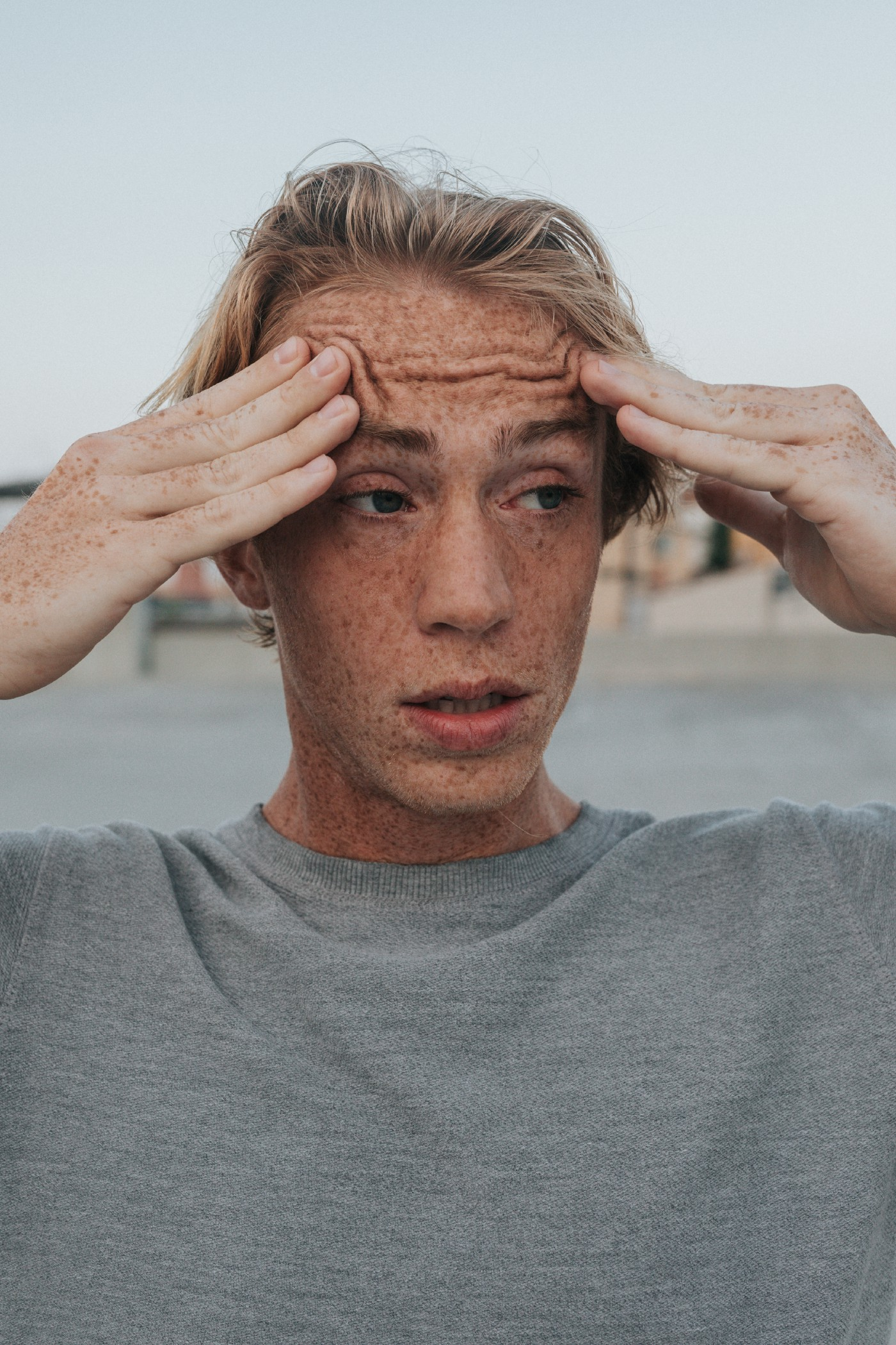 A young caucasian male holding his hands to his head in slight fear and uncertainty.