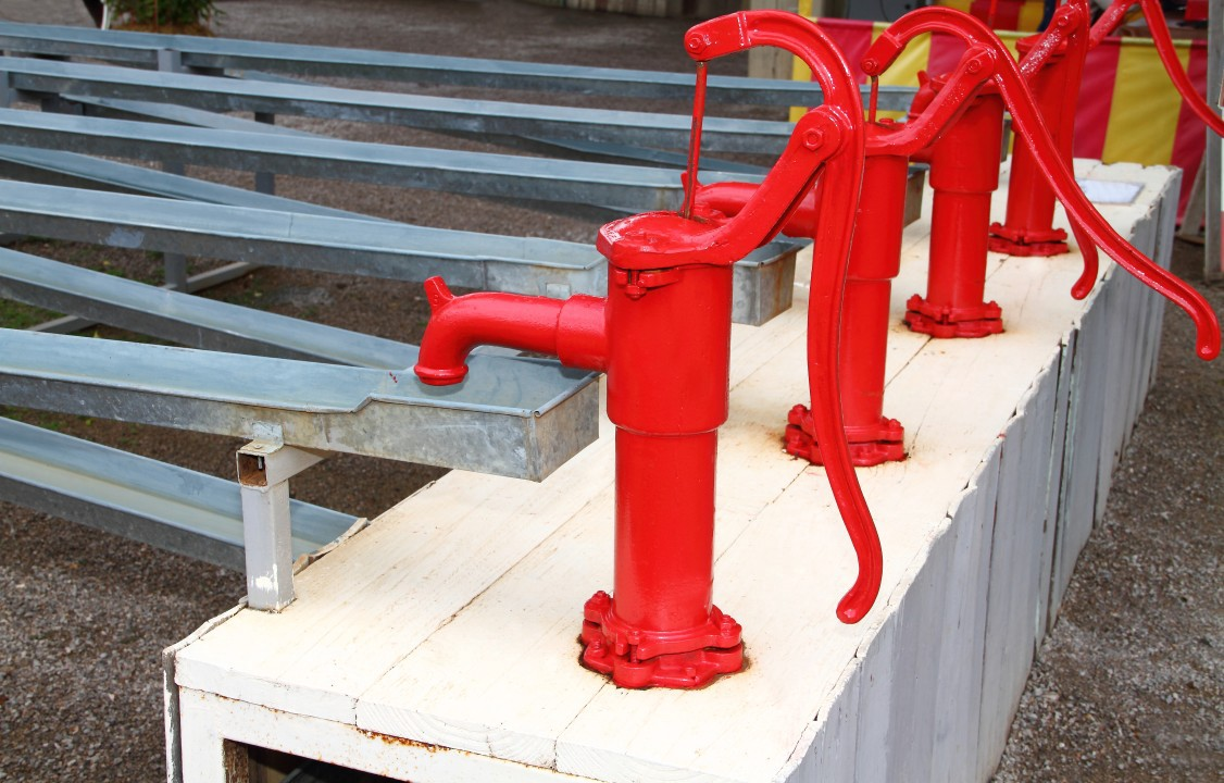 A row of red water pumps. Pull the content capital lever in your business to see new revenue flows.