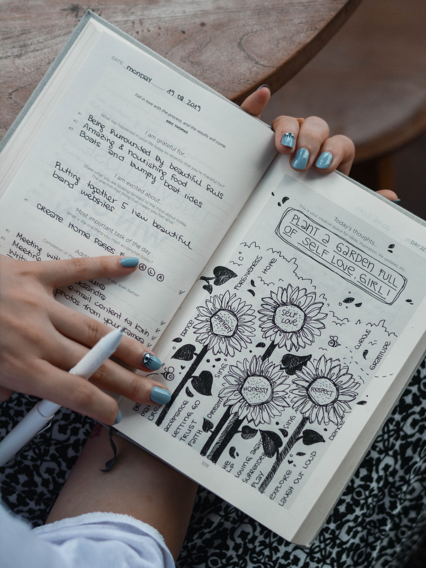 Woman holding an open journal with a drawing about practicing self love.