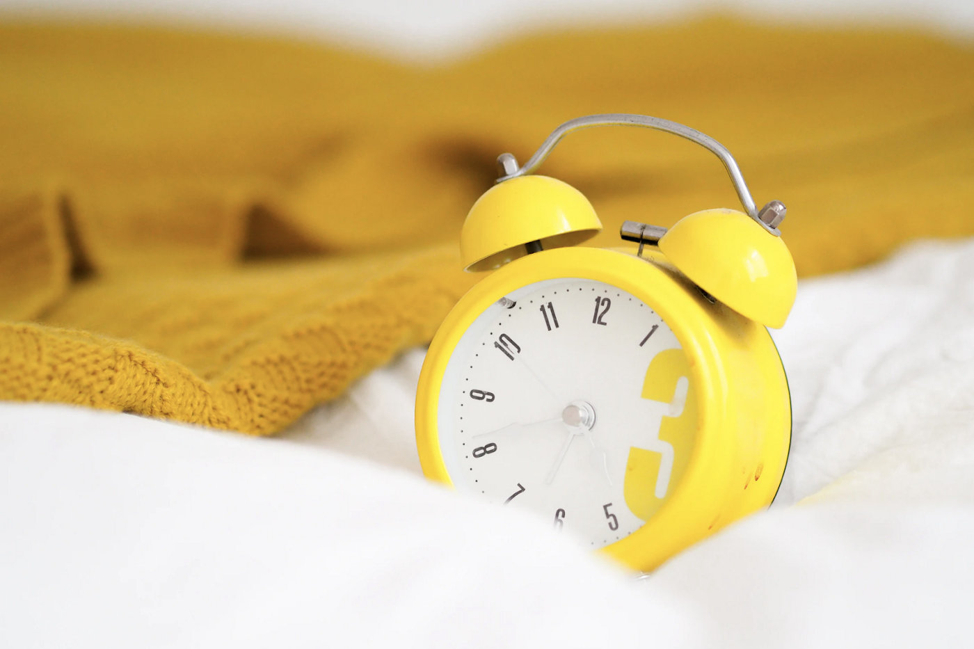 yellow analog alarm clock on a bed