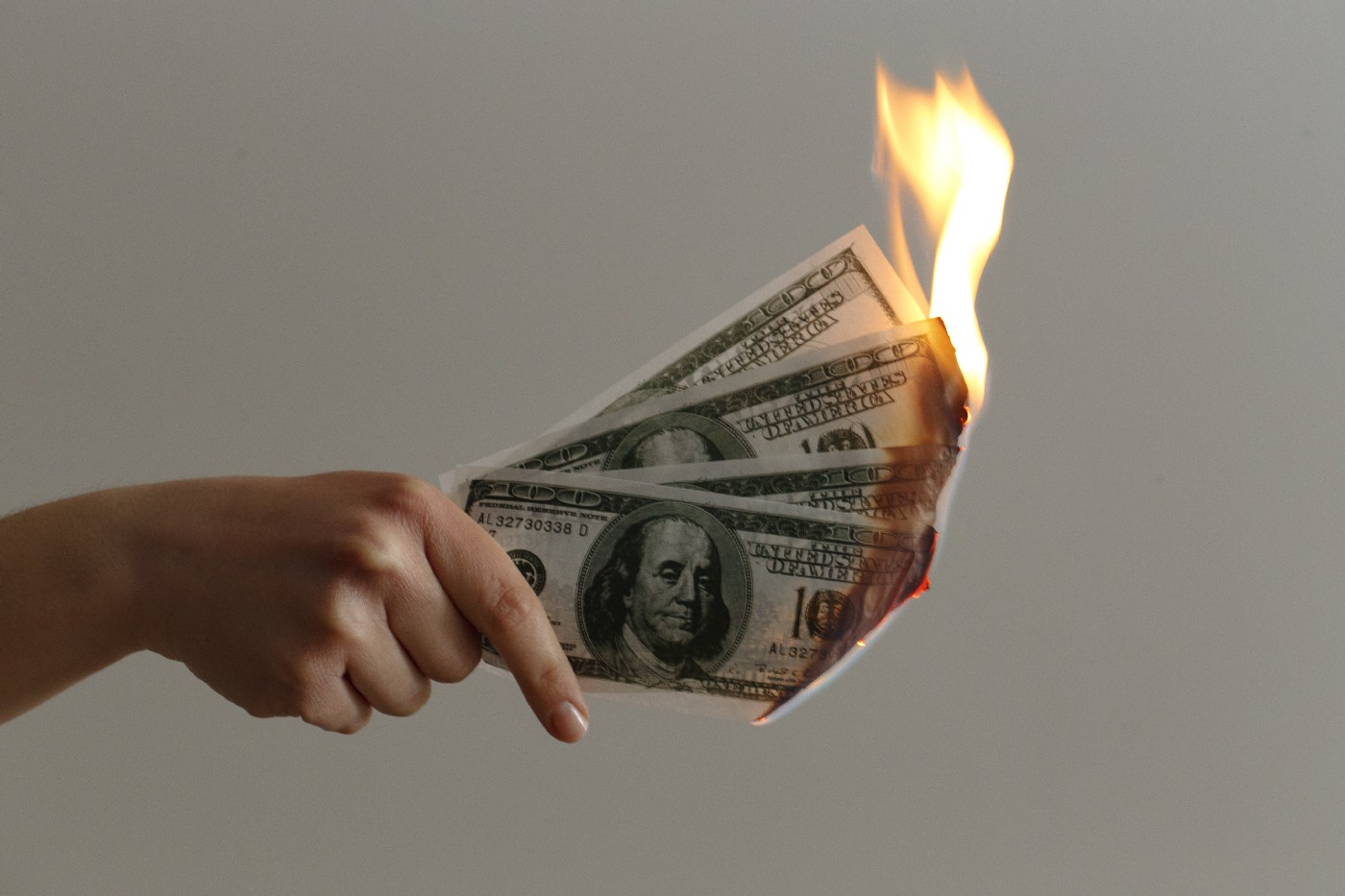 A hand holding money that is on fire.