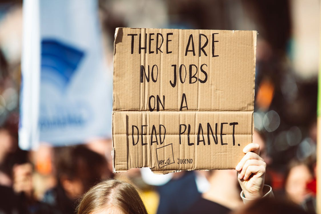 """Protestor holding a homemade sign: """"There are no jobs on a dead planet."""""""