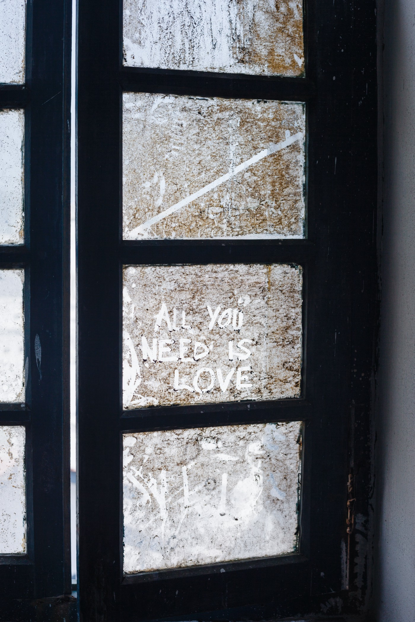 """A dirty window with """"All you need is love"""" written on it."""