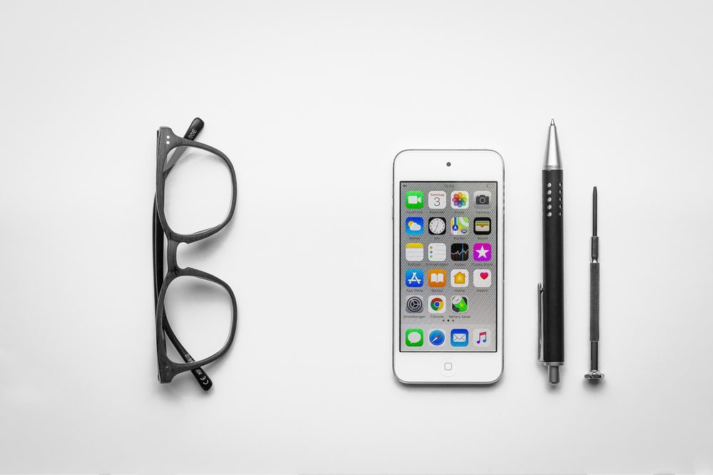 Glasses, I-phone, pen, and screw on a white background