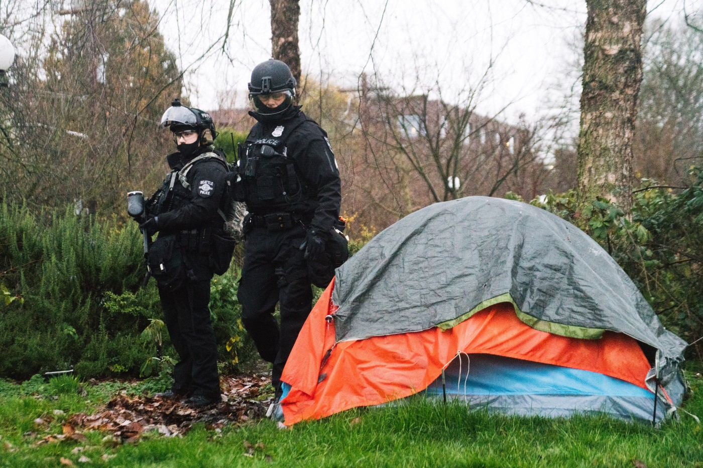 Two officers in riot gear, on with a pepper ball gun walk past an orange and grey tent in Cal Anderson Park.
