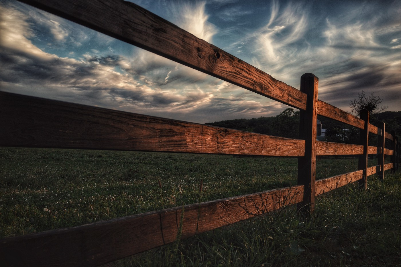 Side view of brown wooden fence through a green field.