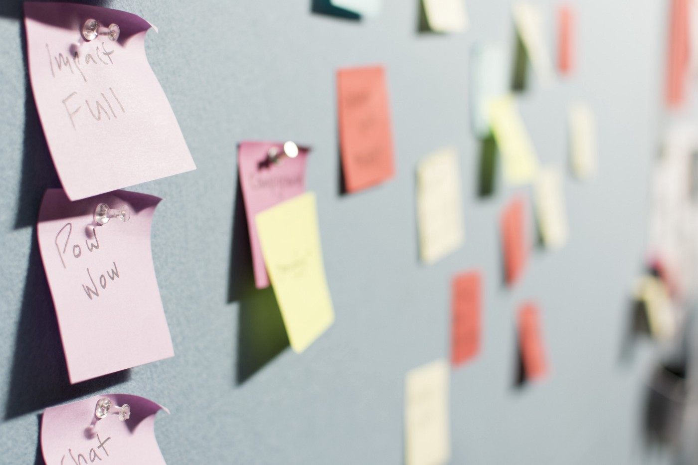 Multicolored Post-It notes thumb-tacked to wall