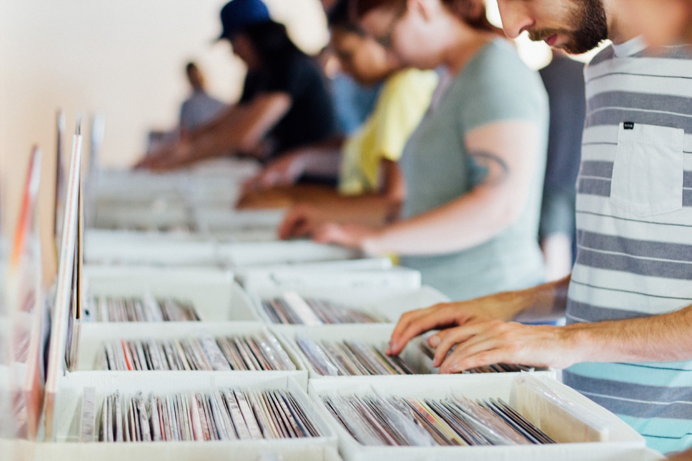 People searching through bins of vinyl records
