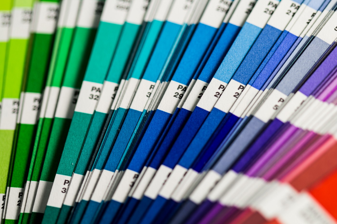 A collection of Pantone color swatches ranging from green to blue, to purple, to red.