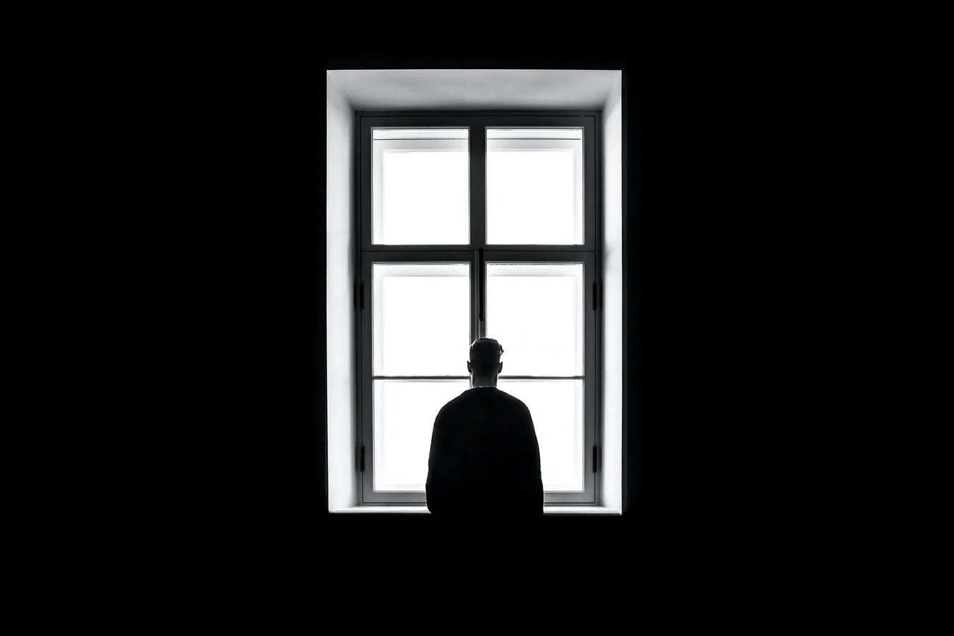 Lonely person in dark room looking through window