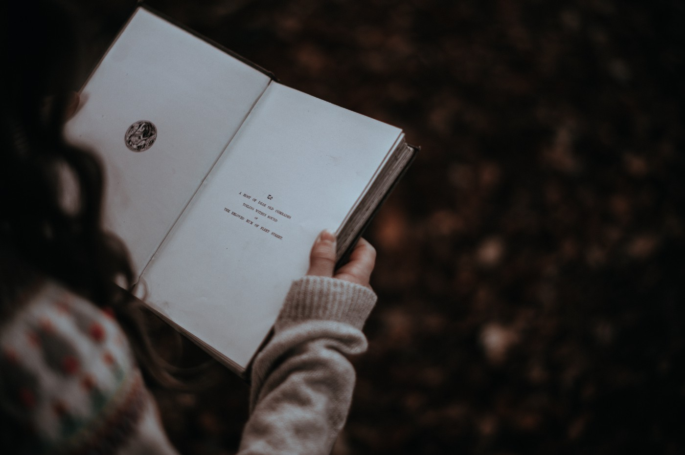 A girl reads the first page of a book.