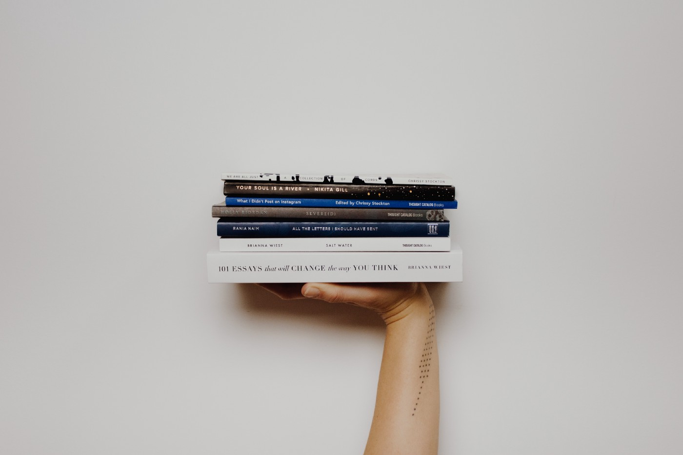 Hand thrusting up stack of books against white background.