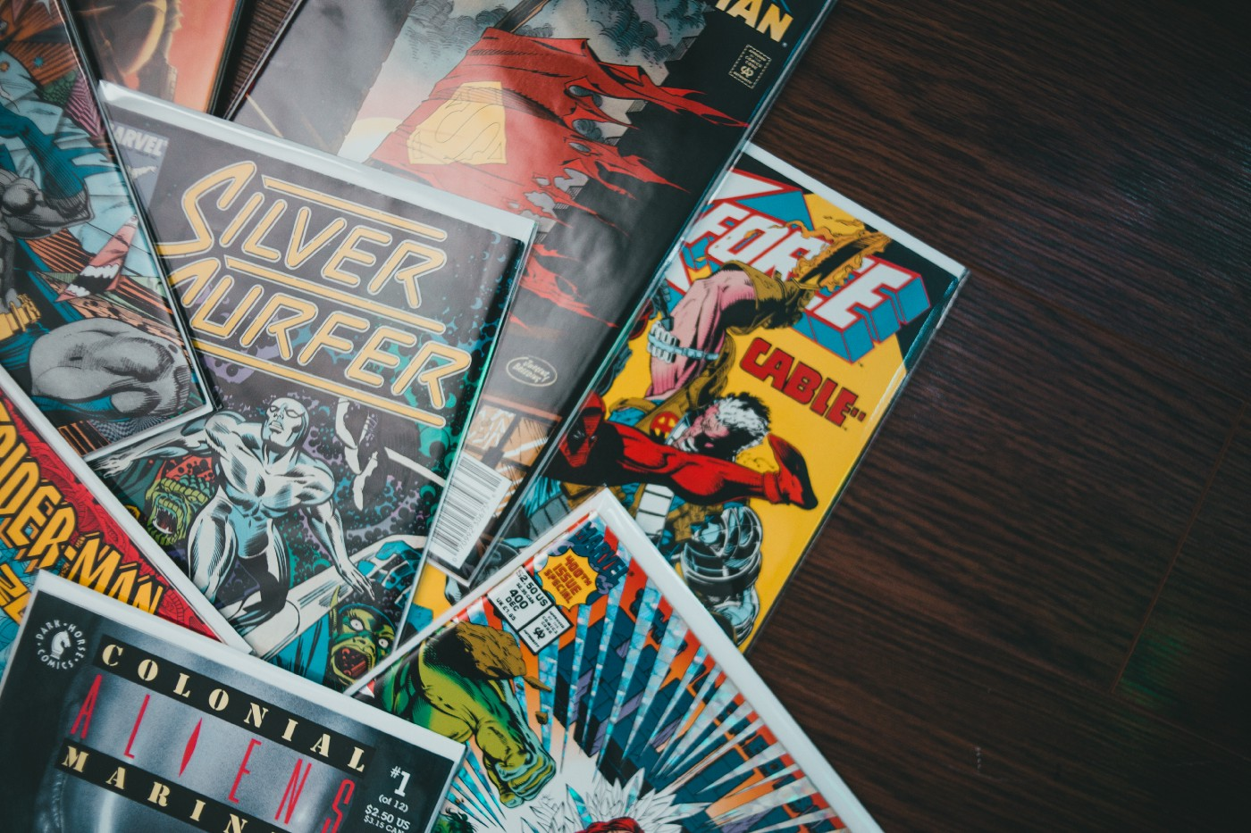 A bunch of comics artistically fanned out on a wooden table