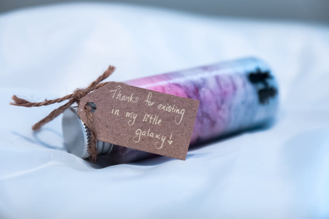 """Thank You note that says """"Thanks for existing in my little galaxy"""" attached to a small, colorful bottle"""