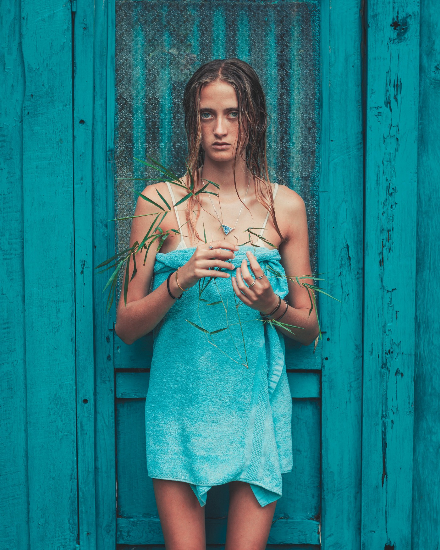 An awkward looking girl standing in front of a teal door with a teal towel wrapped around her nude body.