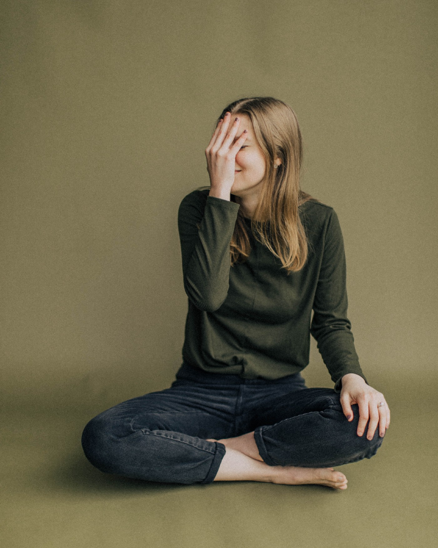 Lady wearing a green jumper, blue jeans sat crossed legged with her right hand covering her face because of shame