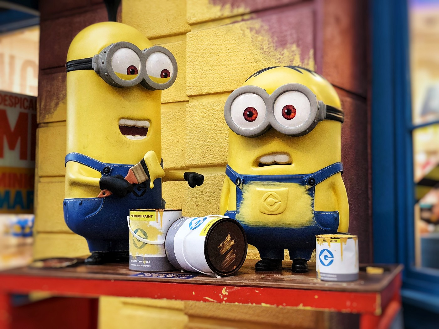 two Minions painting a wall