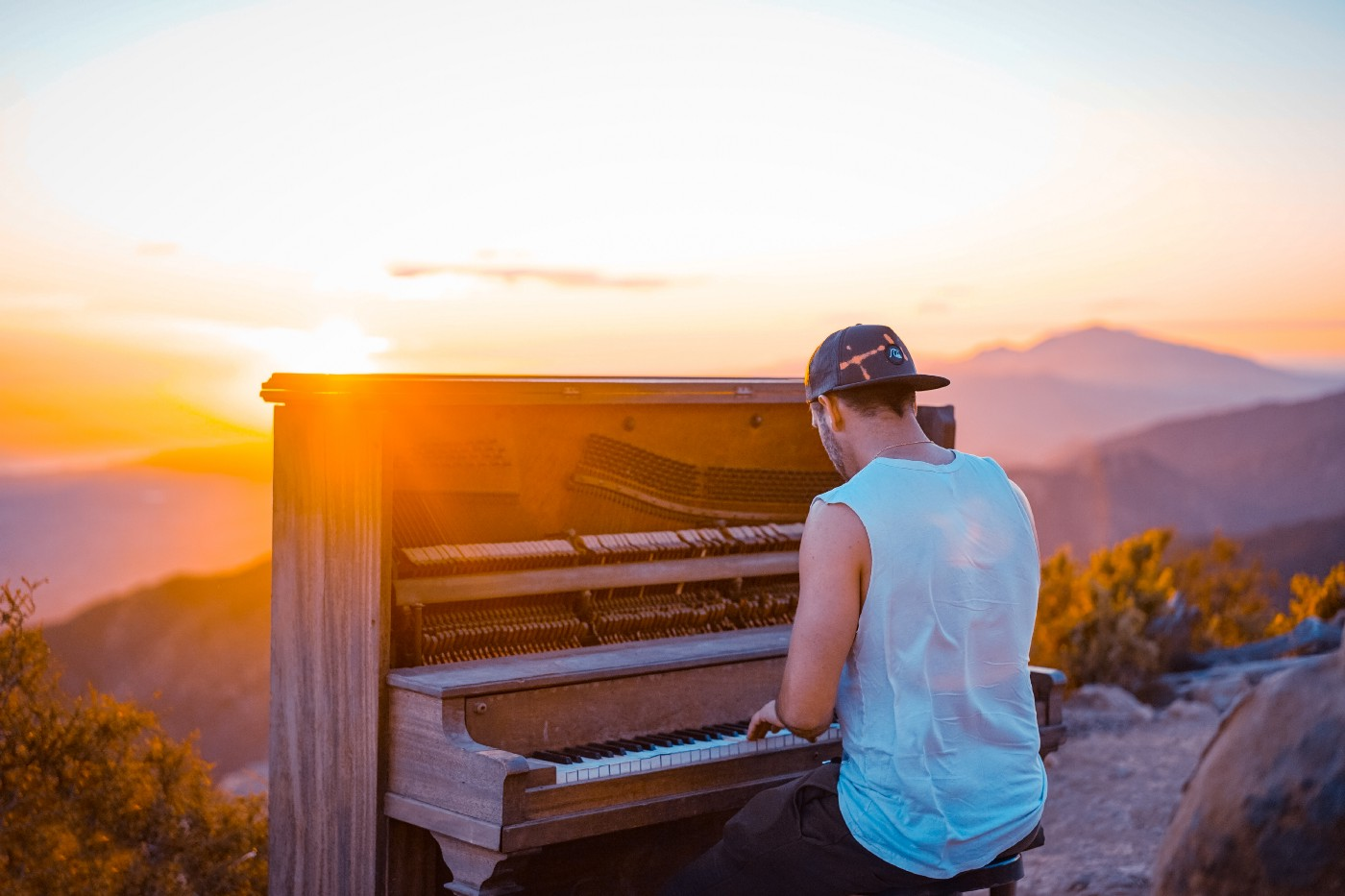 A man playing an organ or piano in front of mountains in the natural air.