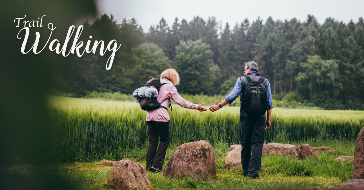 Couple holding hands while walking in a field.