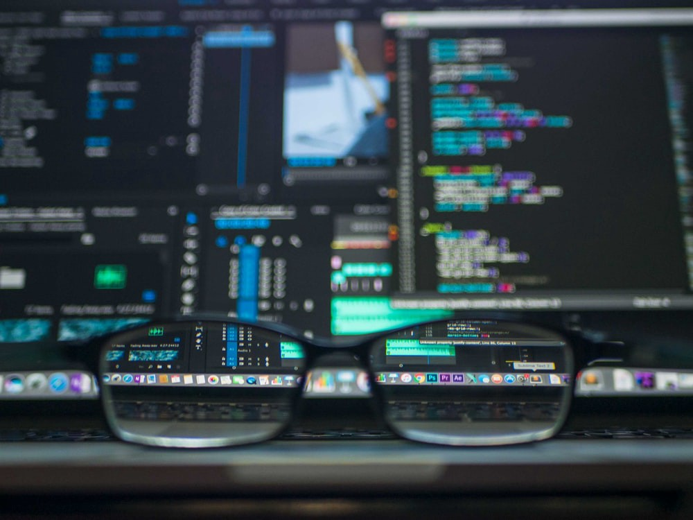 Glasses in front of coding setup