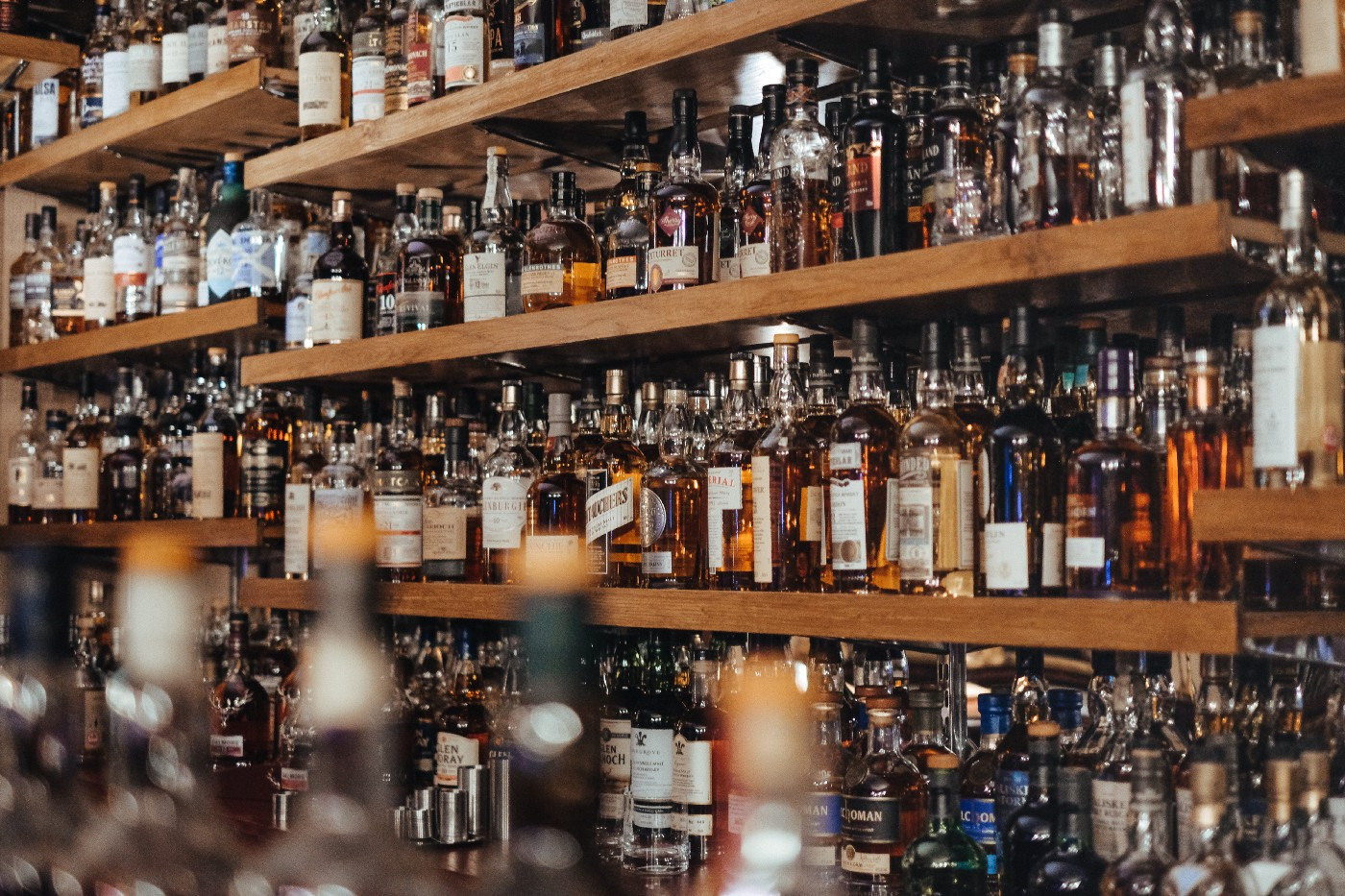 A bar whose shelves are filled with bourbon.