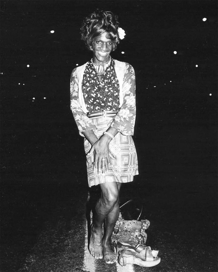 A black and white photo of Marsha P Johnson posing in the middle of the street for the camera. She is wearing a floral shawl, a skirt, and is barefoot. She is smiling and striking a feminine pose.