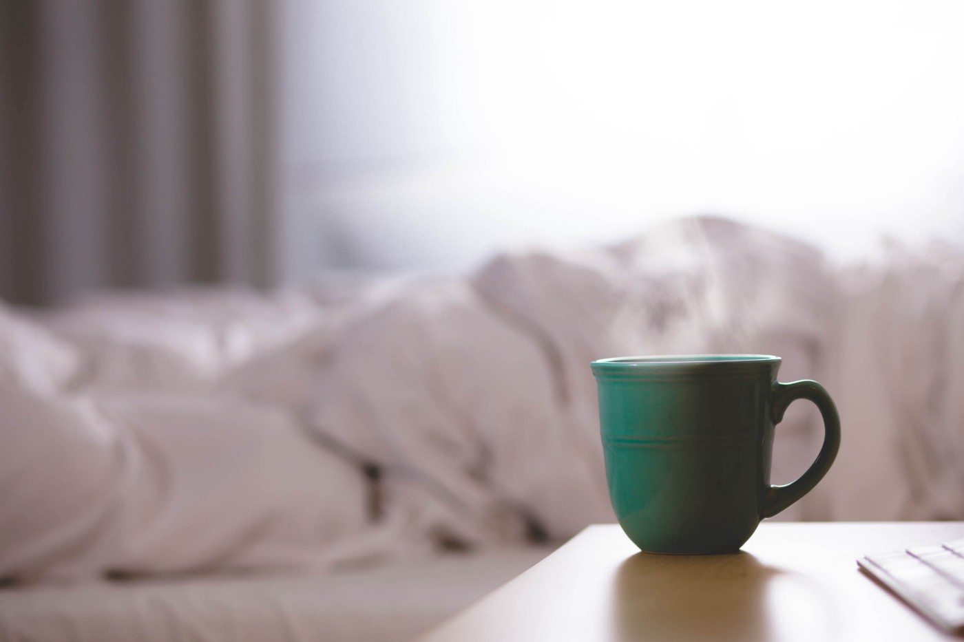 A green cup on a bedside counter in the foreground. Ruffled bedsheets in the background.