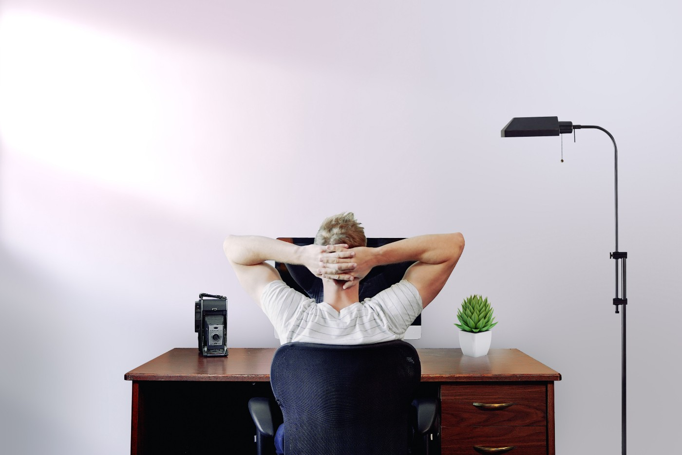 Man sitting at a desk with his hands behind his head.