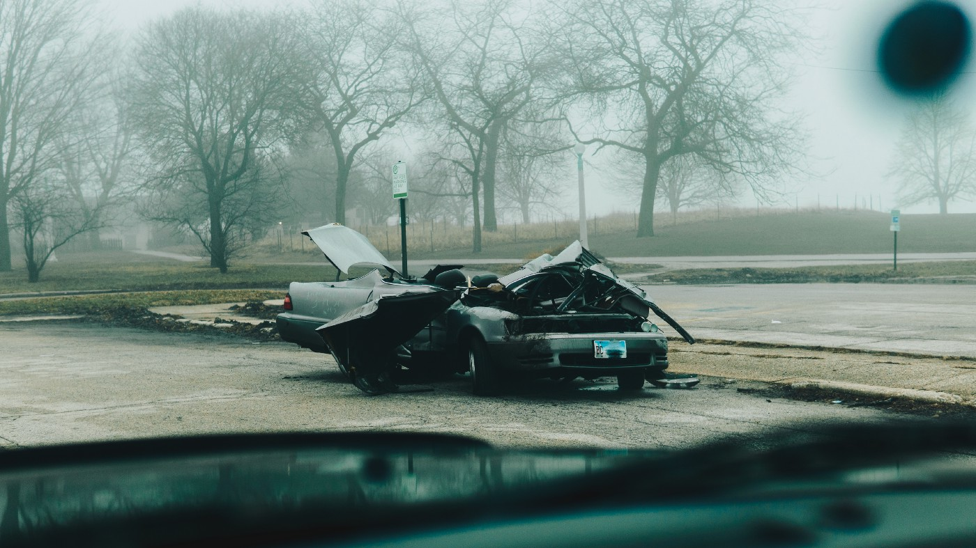 A photo of two cars in a T-bone collision with trees in the background.