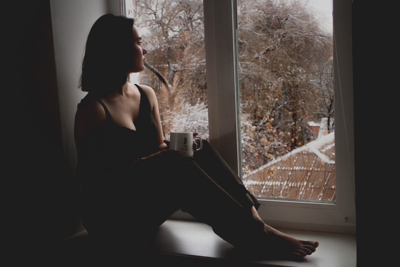 A woman sitting on a window sill looking out at snowy roof-tops and trees