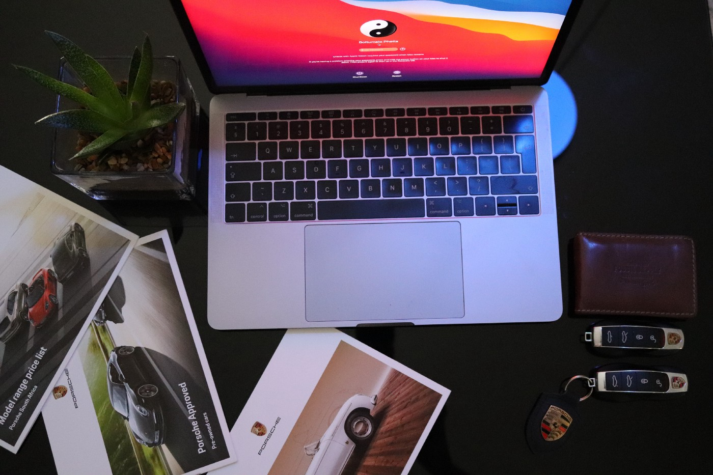 An open laptop surrounded by photos of cars