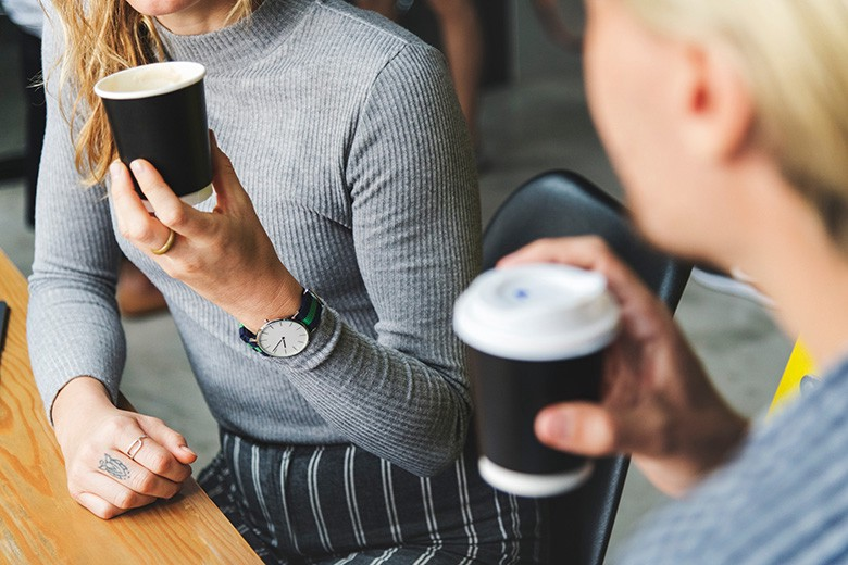 Two people chatting over take away coffee