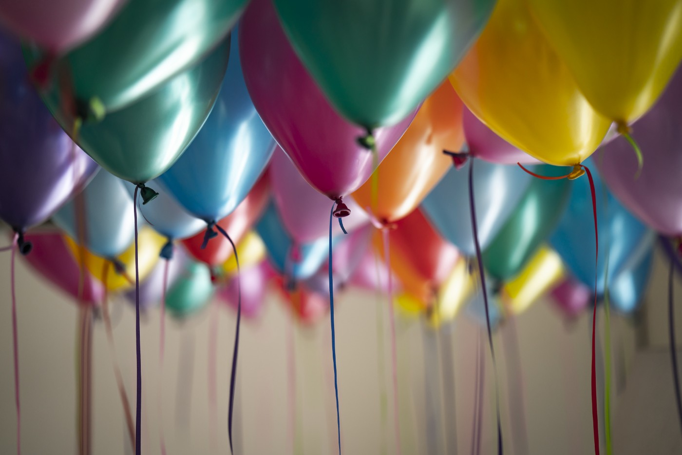 Side angle of various colored balloons filing a dimly ceiling space. Colors include teal, yellow, pink, orange, red and blue.