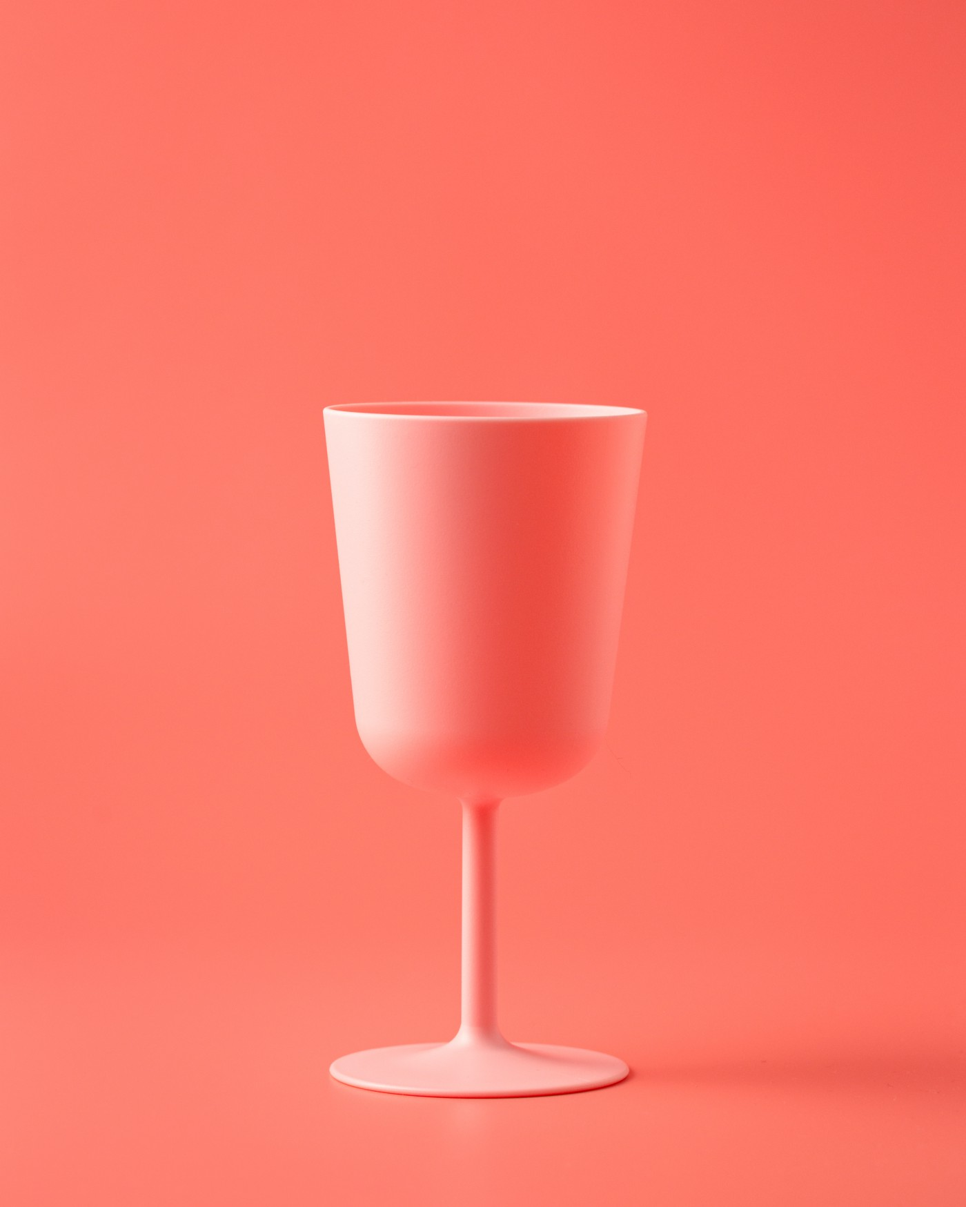 A rendering of a coral cup of wine on a coral background.