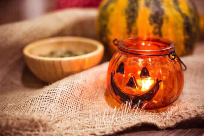 Jack-o-lantern holding a lit candle, bowl, and gourd on burlap
