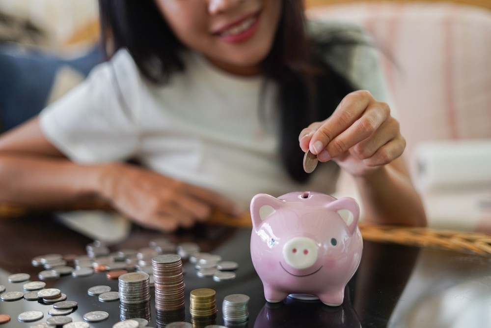 A girl smiling and putting coins into her piggy bank.