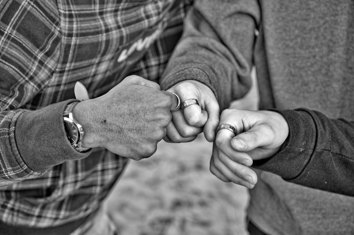 Black and white photo of three people bumping their fists.