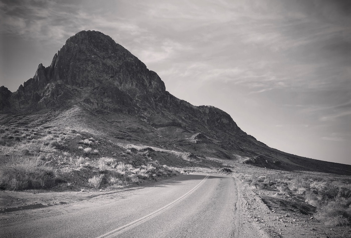 A black and white photo looking down a curvy desert road with a rocky mountain peak in the distance.
