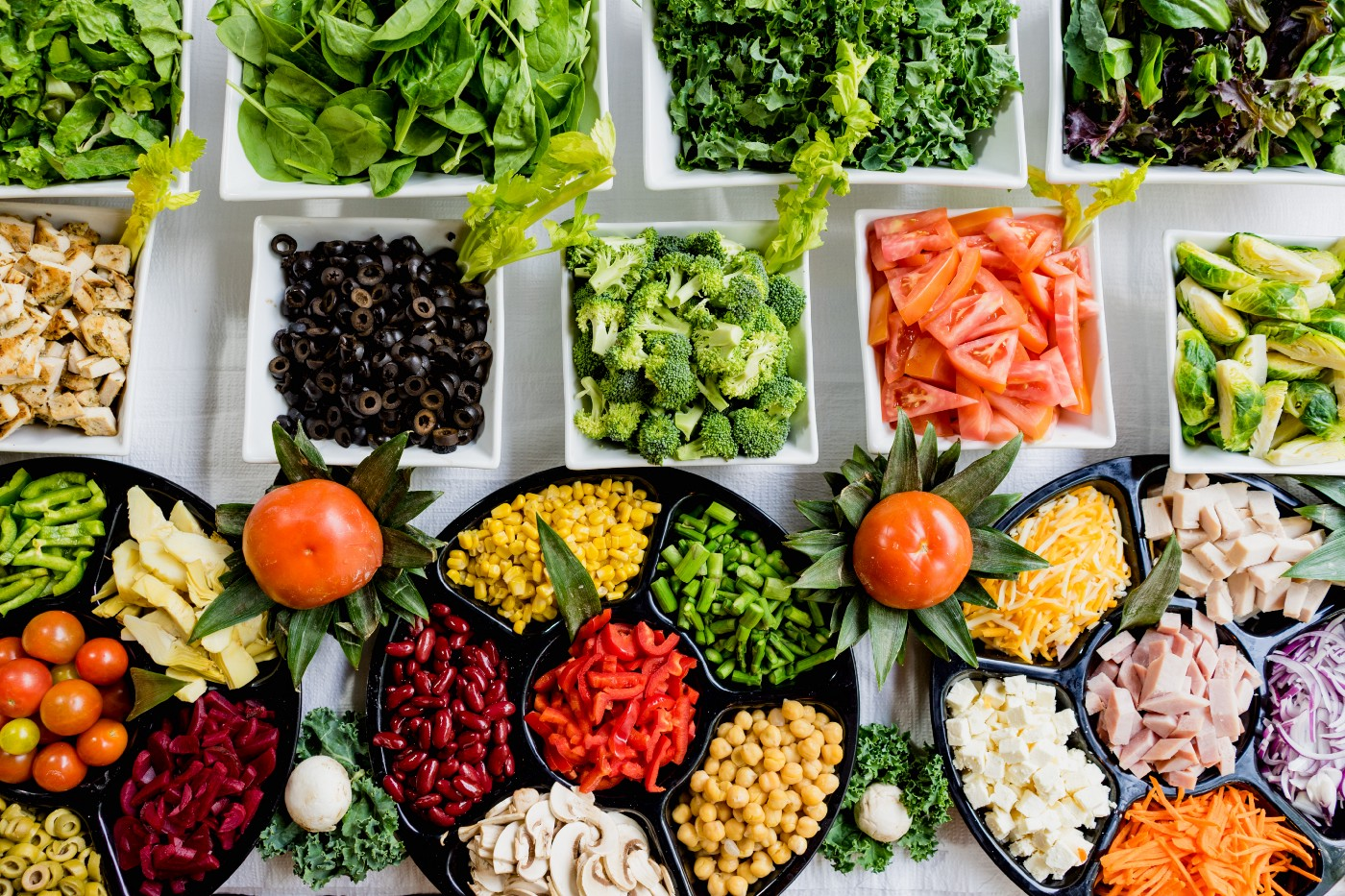 various vegetables and fruits; carrots, broccoli, tomato, celery, black olives, spinich and onions; all set in black and white bowls.
