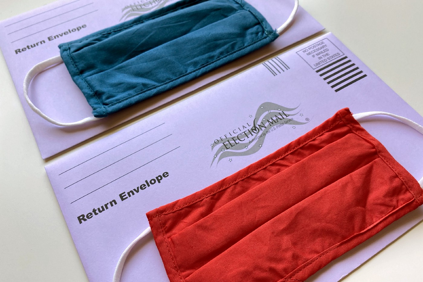 America's voting experience in 2020 will be unlike any other in history. Ballots shown with masks on top of the envelopes.