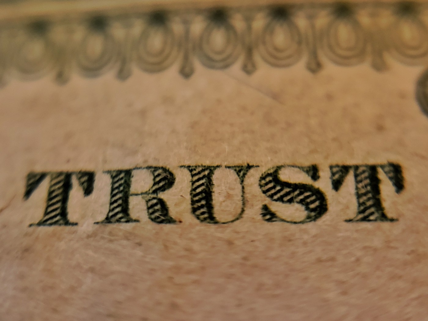 A closeup picture of the word Trust on a United States dollar.